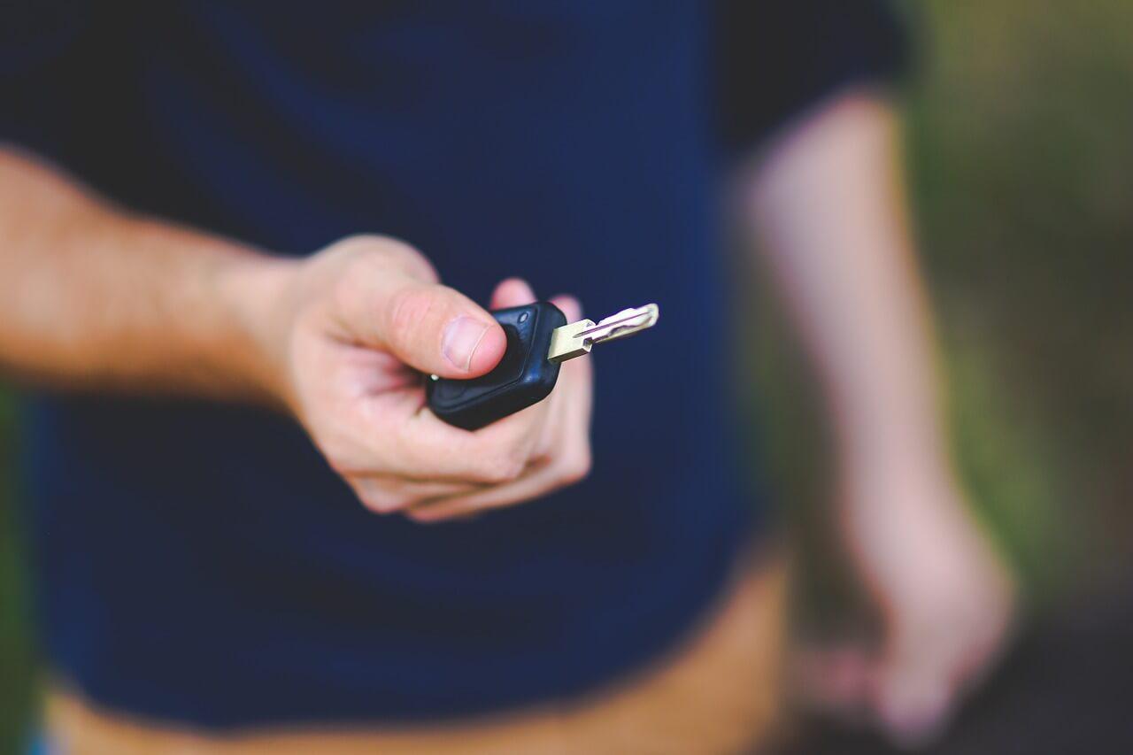 אדם מחזיק מפתח רכב שחור